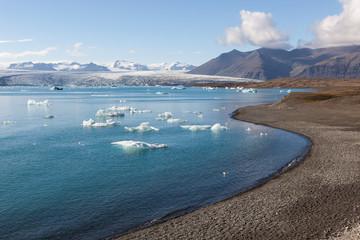 Scattered melting icebergs near Jokulsarlon glacier lagoon shore. Base of the Vatnajokull glacier at Jokulsarlon, Iceland.