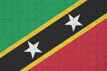 Saint Kitts and Nevis flag  is depicted on a folded puzzle