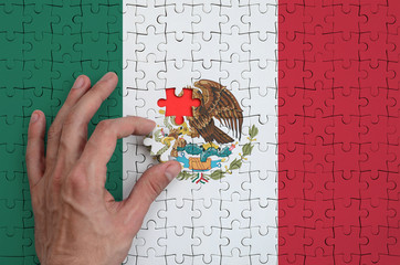 Mexico flag  is depicted on a puzzle, which the man's hand completes to fold