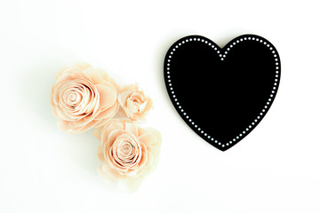 Black love heart with three artificial flowers beside it on a white surface