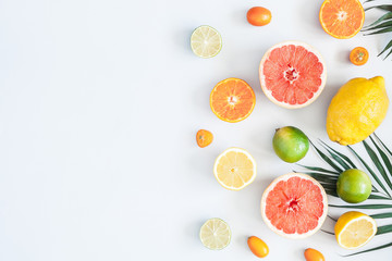 Fruit background. Colorful fresh fruits and tropical palm leaves on pastel blue background. Summer concept. Flat lay, top view, copy space