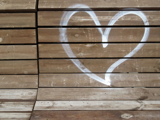 Heart painted on the wooden bench. Symbol of love