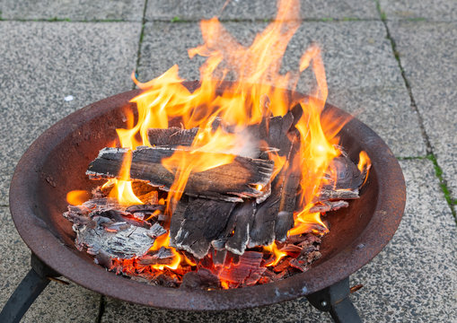 Wood burning brightly in a metal fire pit