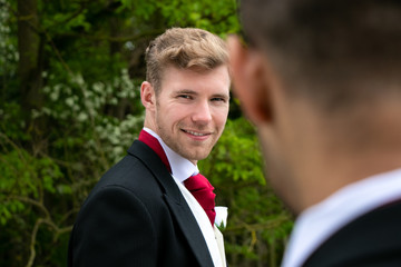 Gay couple of grooms pose for photographs on their wedding day