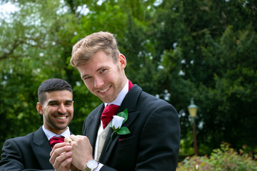 Gay couple of grooms pose for photographs after their wedding ceremony