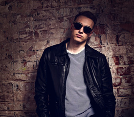 Male model posing in leather jacket and trendy eyeglasses on brick wall street background. fashion toned contrast portrait with empty copy space