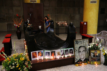 Woman walks by the grave of slain Salvadorean Archbishop Oscar Arnulfo Romero as pictures of him and other murdered priests are displayed during a vigil to await the announcement of his canonization date, in San Salvador