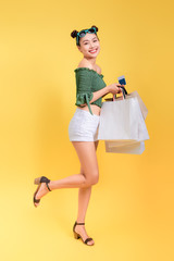 Full length portrait of a cheerful attractive woman holds shopping bags and a credit card on yellow background
