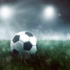 Soccer ball on grass with mist and spotlights