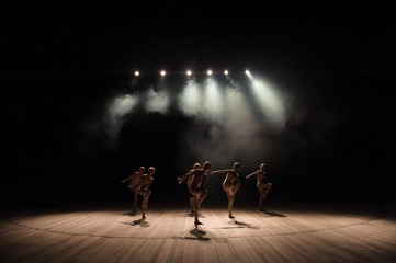 A group of small ballet dancers rehearses on stage with light and smoke