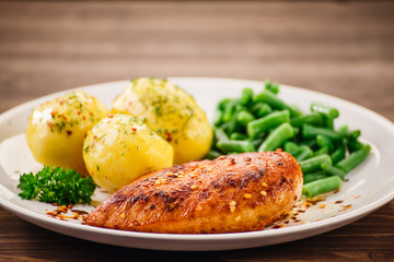 Grilled chicken fillet and vegetables on wooden table