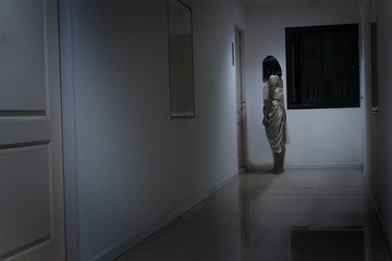 Horror woman wearing Thai traditional costume, standing in front of the door, Thai ghost concept