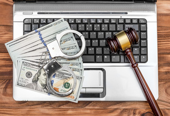 Laptop with handcuffs, gavel and money on wooden table. Top view.