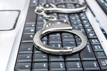 Handcuffs on the laptop's keyboard. Cyber crime concept. Close up.