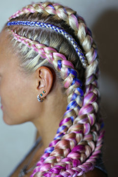 a beautiful hairstyle made of thick and thin braid on the head with a colored kanekalon, hair is woven in material, hair bands