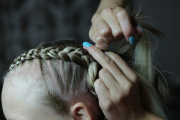 girl with blonde hair, process of braiding braids with kanekalon, fashion braids, hands close-up at work, hairdresser