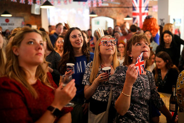 People gather to watch the wedding of Prince Harry and Meghan Markle at Windsor castle at the Book Club in London