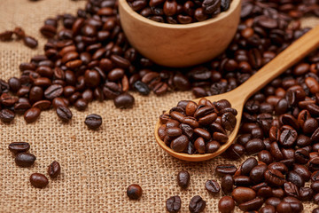 Wooden bowl with roasted coffee beans on rustic background.