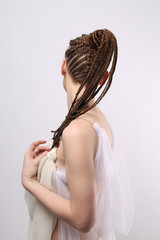 photo shoot of a girl on a white background with an exotic hairdo in an African style, a girl of European appearance