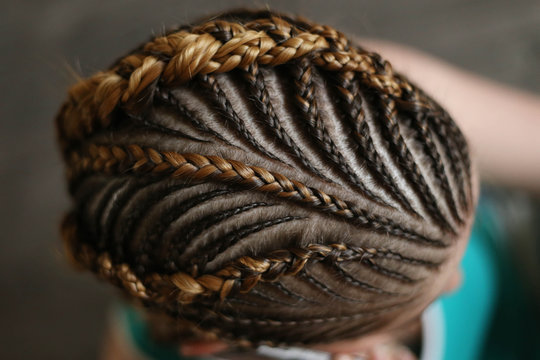 hairstyles from thin plaits on the head of a girl, a master, a beauty salon, a beauty trail