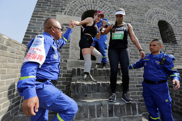 Rescuers help Portuguese runner Adriele Silva through a tower during the Great Wall Marathon in Jixian of Tianjin