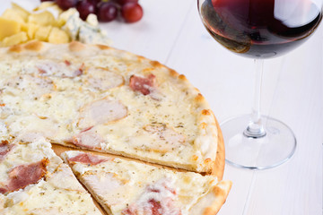 Fresh cheese pizza with ham and cream sauce on wooden board and glass of red wine, close up. Italian traditional cuisine, copy space. Food, shallow depth of field