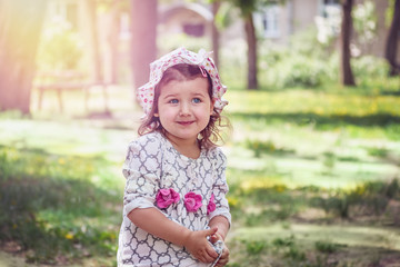 Portrait of a little caucasian girl appearance in a dress with a shy smile. Toned. Close-up