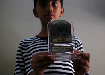 Ali Aziz Shaikh 12, brother of Sabika Aziz Sheikh, a Pakistani exchange student, who was killed with others when a gunman attacked Santa Fe High School in Santa Fe, Texas, U.S., poses for a photo with her shield prize at their residence in Karachi