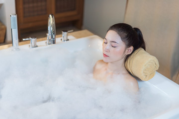 woman relaxing with eyes closed in bathtub