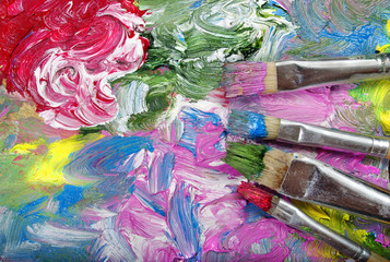 a palette of artists and brushes. brush strokes close up.