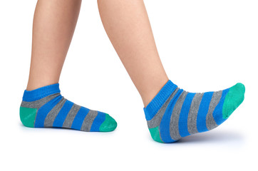 Kid legs in striped socks isolated on white background