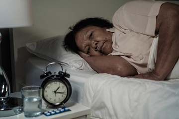Old woman suffering from insomnia is trying to sleep in bed