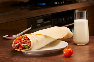 Shawarma with meat, tomato, onions and parsley on dark table