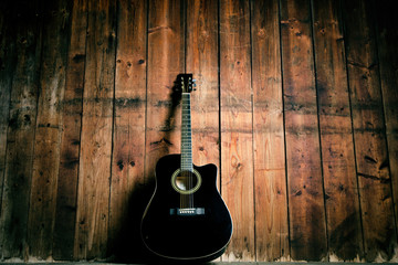 Acoustic guitar on a wooden texture with copy space for a text. Music and leisure concept. Guitar against wooden wall.