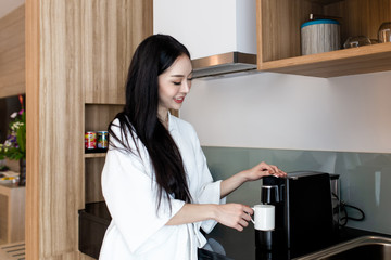Beautiful asian woman making coffee for breakfast in the kitchen at home