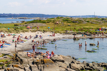 Beach on the Swedish west coast with people sunbathing and bathing