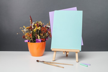 paints, brushes, and a sheet of paper on an easel