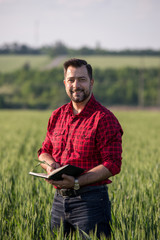Young handsome farmer with diary standing in wheat field