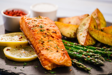 Grilled salmon with vegetables on wooden table
