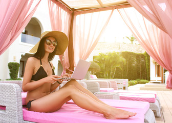Work and travel. Incredibly sexy girl in a black bikini sits with a laptop near the pool. Find a tour. The blogger. Vlog. Communication. Recreation. Resort. Delicate shiny skin. Brunette.