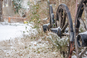 wooden wheels of the wagon covered with snow