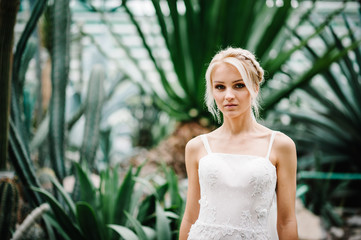 Woman stand in the Botanical green garden full of greenery. Wedding ceremony. Portrait attractive blonde bride standing in a wedding dress on the background of greenery.