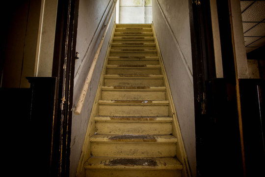 Old dirty damaged abandoned wooden stairs to the garret. Entrance to the attic.