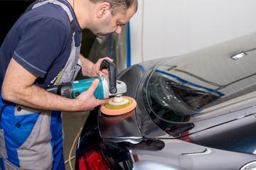 A man polishes a black car with a polisher