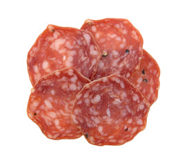 Slices of uncured soppressata dry salami in a group top view isolated on a white backgroun