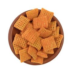 Top view of cheddar cheese crispy rice crackers in a small bowl isolated on a white background.