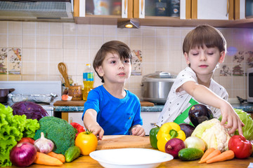 Healthy eating. Happy children prepares and eats vegetable salad in kitchen