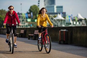 Two women cycling in city