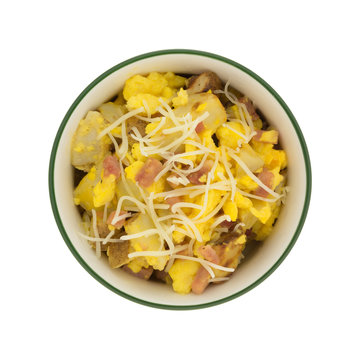 Top view of a bowl of scrambled eggs with potatoes and ham plus cheese isolated on a white background.