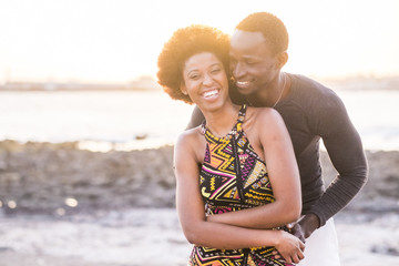 black race african afroamerican couple in relationship or partnership or friendship touching and enjoying the sunset on the beach in vacation outdoor leisure time